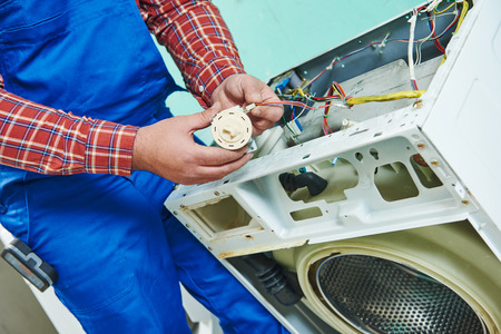 repairman fixing a washer and dryer unit